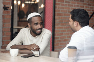Smiling Black bearded man in kufi sitting with rosary beads at table and listening to Arabian friend in cafe