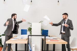 2 Kollegen streiten im Büro und werfen Papier, fehlender Teamgeist